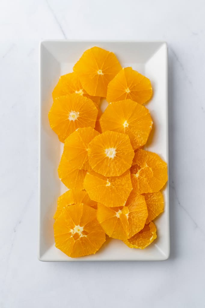 Overhead view of slices of oranges on a white platter.