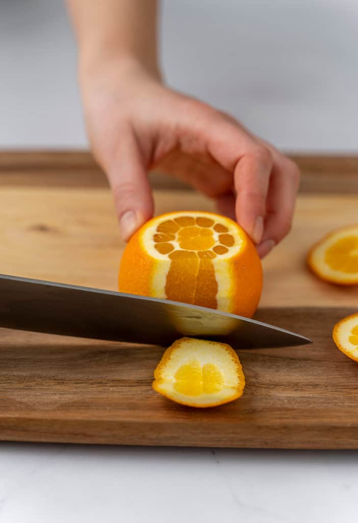 The side of the orange peels being sliced off.