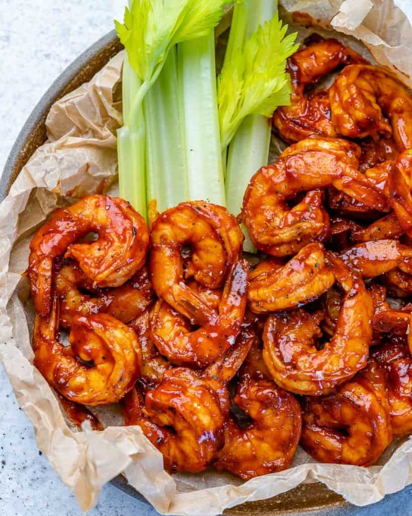 top view shrimp in a plate lined up with brown parchment paper