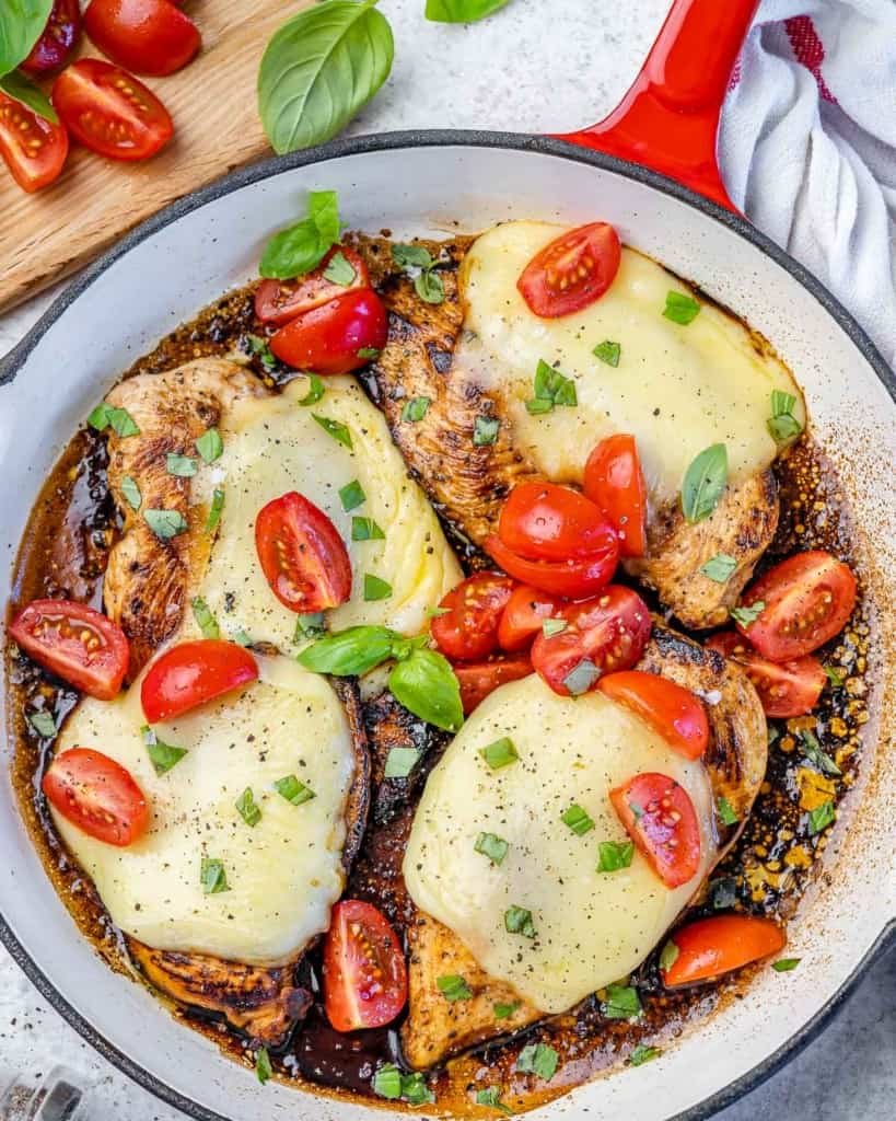 Top view of chicken caprese in red pan with tomatoes and basil