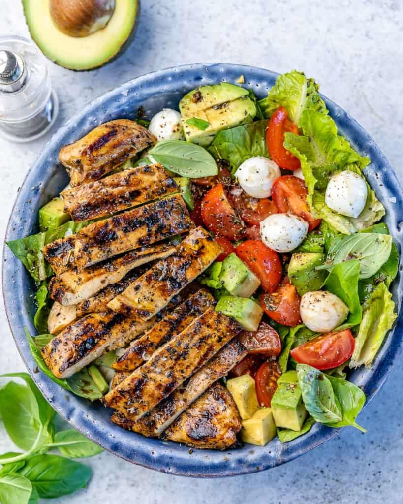 top view of salad in a blue bowl with sliced grilled chicken