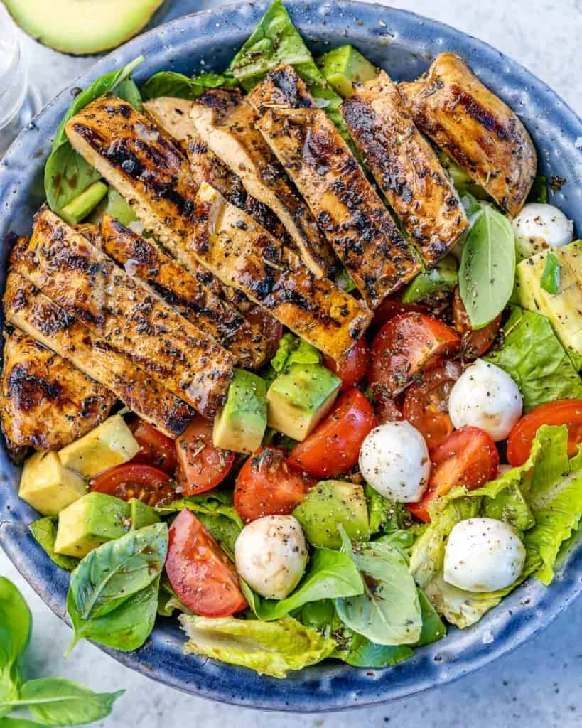 top view caprese salad topped with grilled chicken