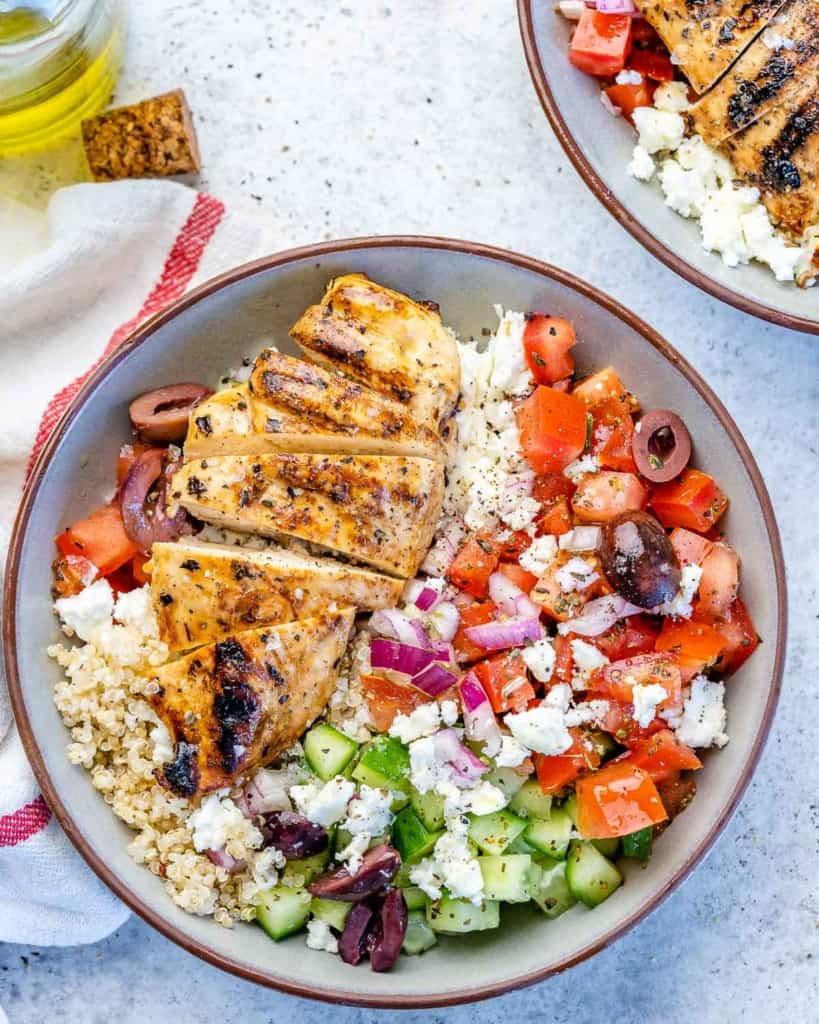 One bowl filled with Greek chicken and vegetables