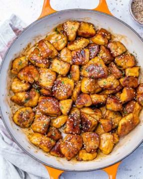 top view honey chicken bites in an orange skillet