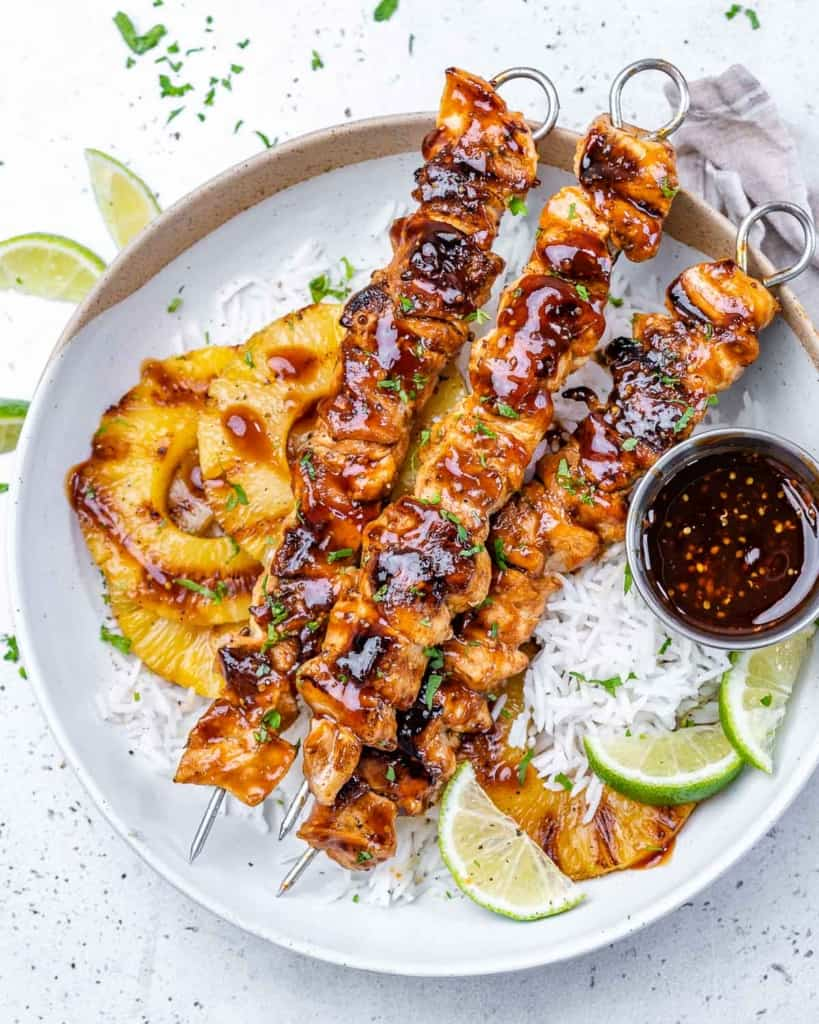Three skewers with chicken on rice
