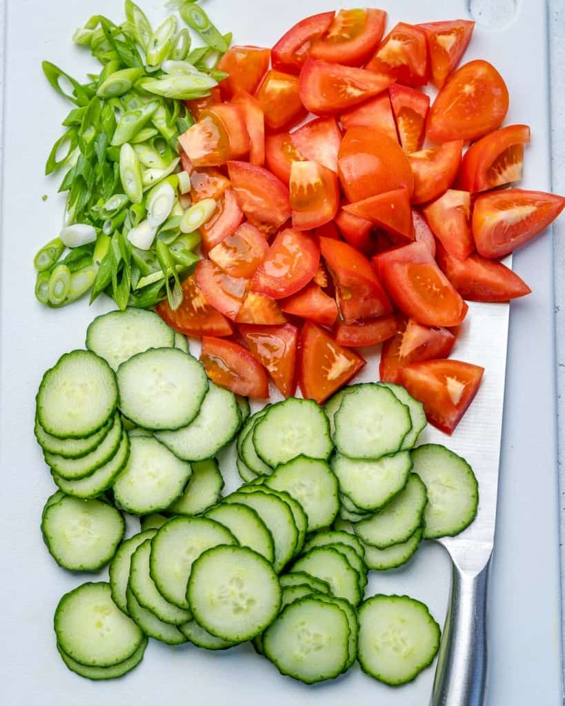chopped tomatoes, cucumber, and onions on platter