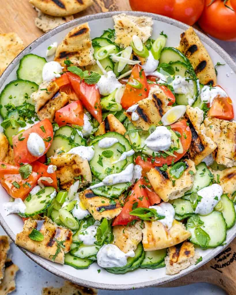 top view chopped salad with naan bread and creamy dressing on a white plate