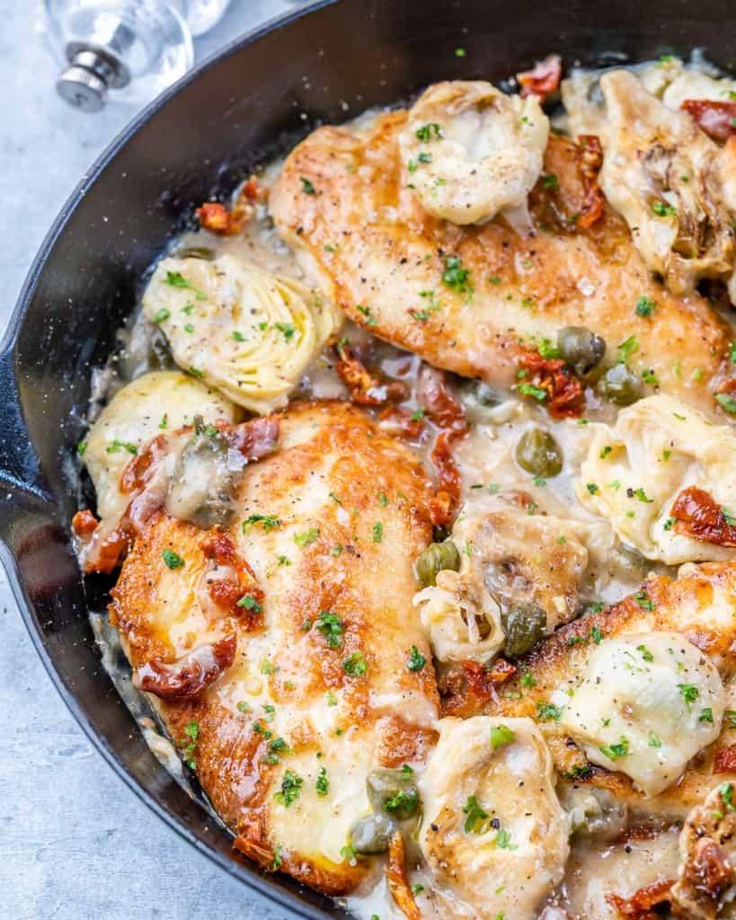 side shot of chicken in a creamy lemon sauce with artichoke