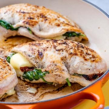 side shot of tuscan stuffed chicken in orange pan