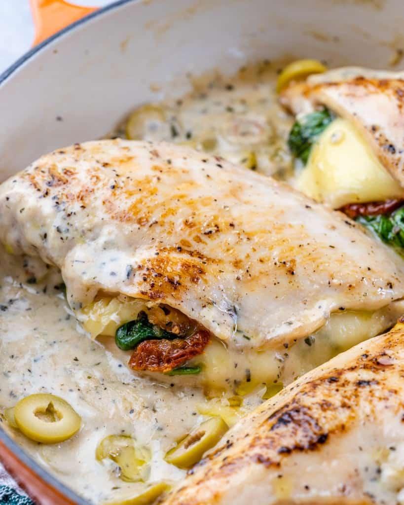 side shot of chicken stuffed breast in a creamy sauce