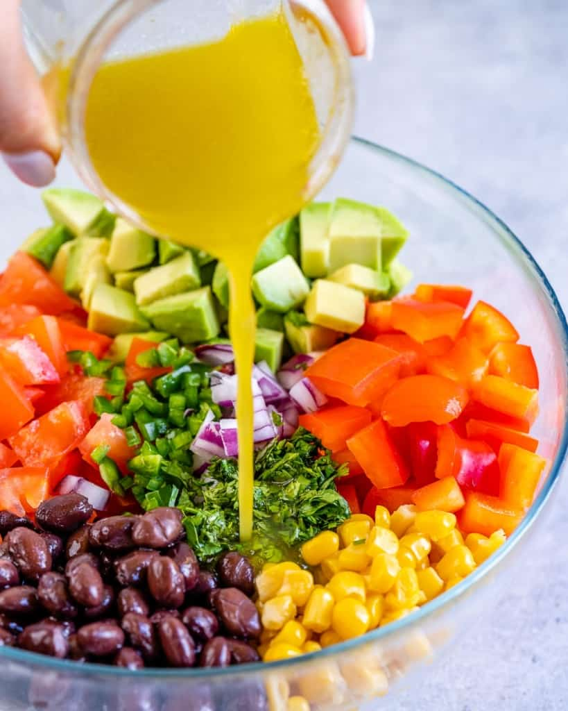 dressing being poured over bowl of chopped veggies