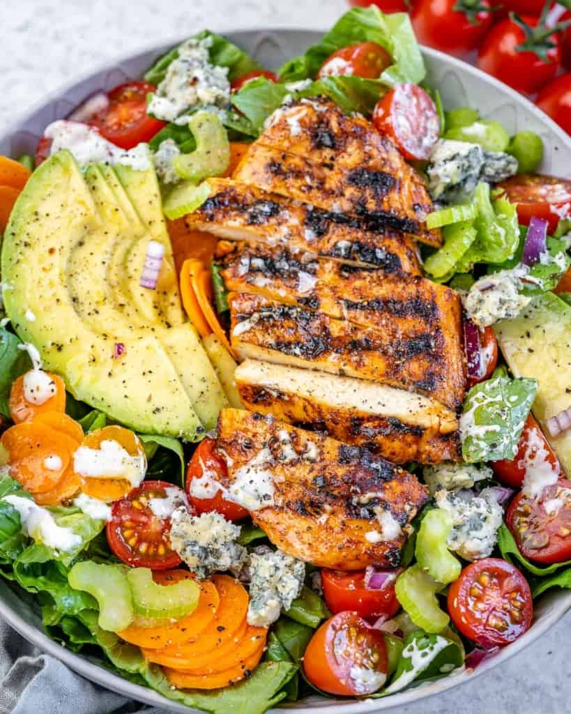 close up grilled chicken salad with avocado and blue cheese