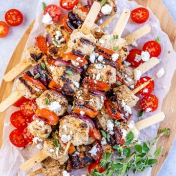 top view chicken skewers with tomato garnishes and feta cheese on a brown cutting board