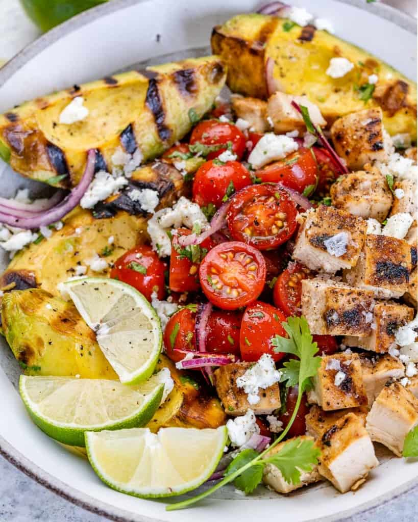 one bowl of grilled avocado chicken salad with tomatoes and feta cheese