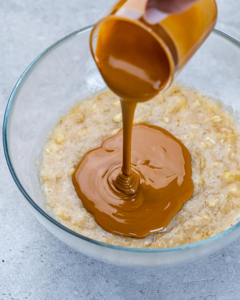 peanut butter being poured over mashed bananas