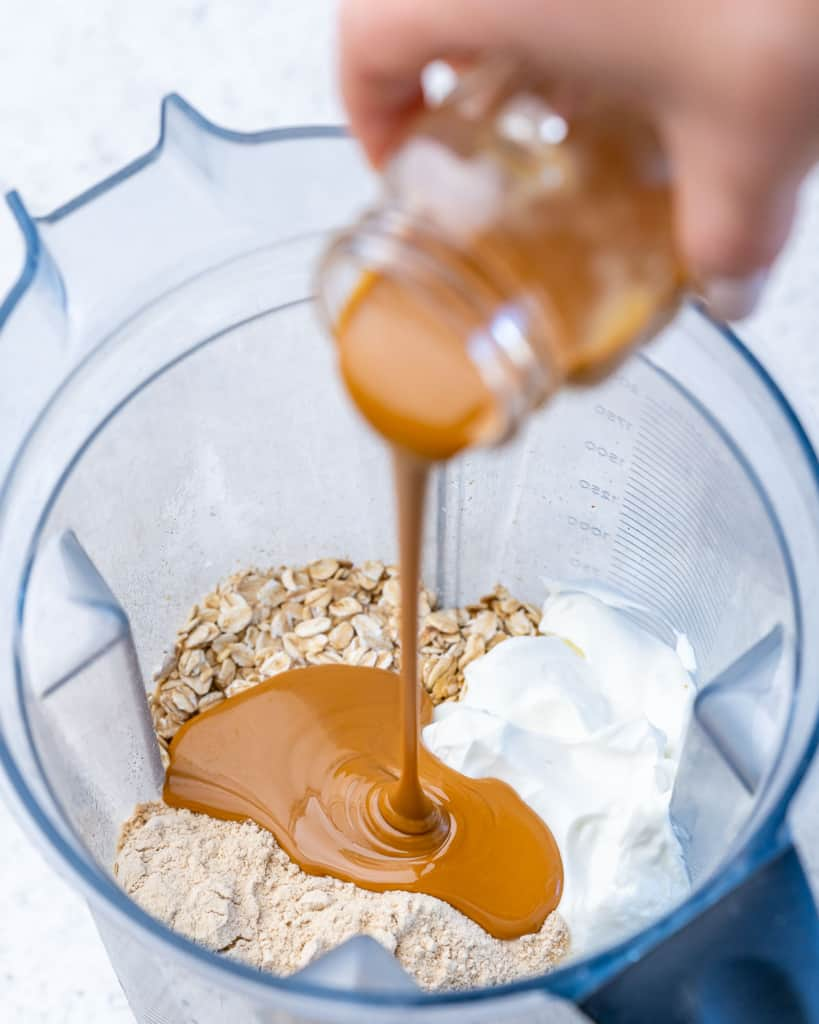 ingredients to make overnight oats with peanut butter being poured into the blender