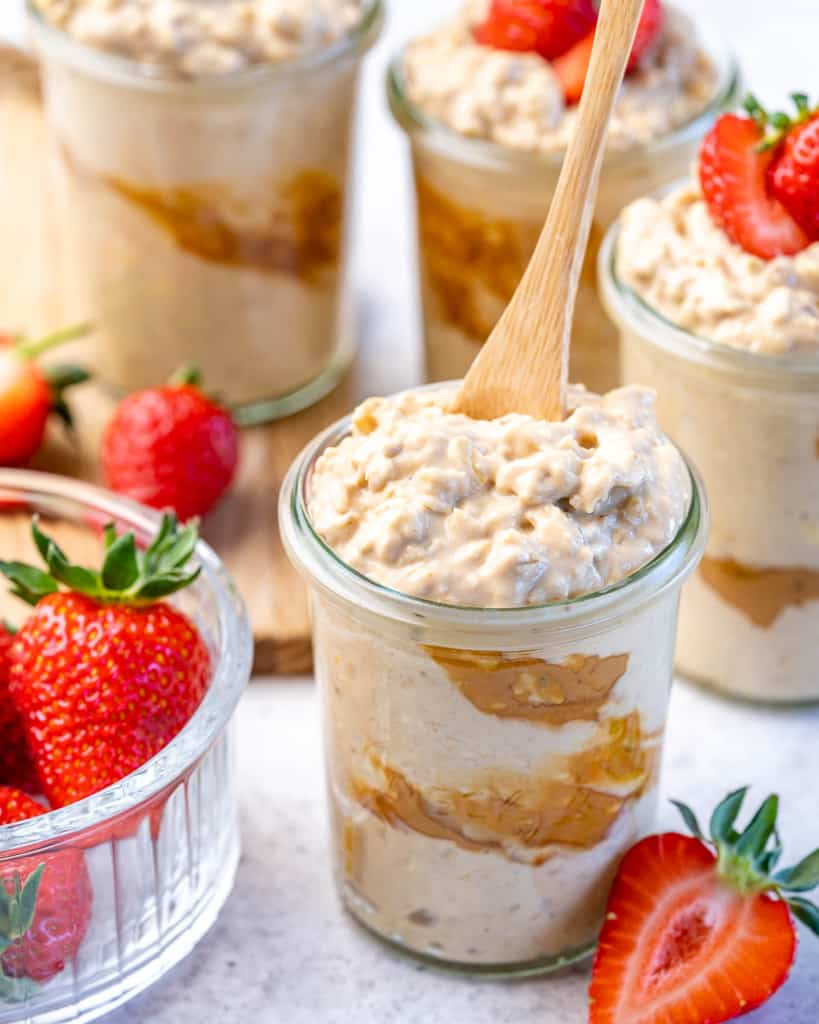 spoon in a jar containing overnight oats with a side of fresh strawberries