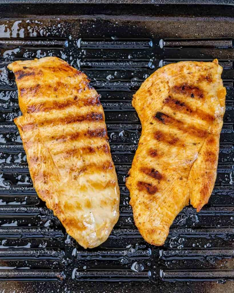two grilled chicken breast on a grill pan