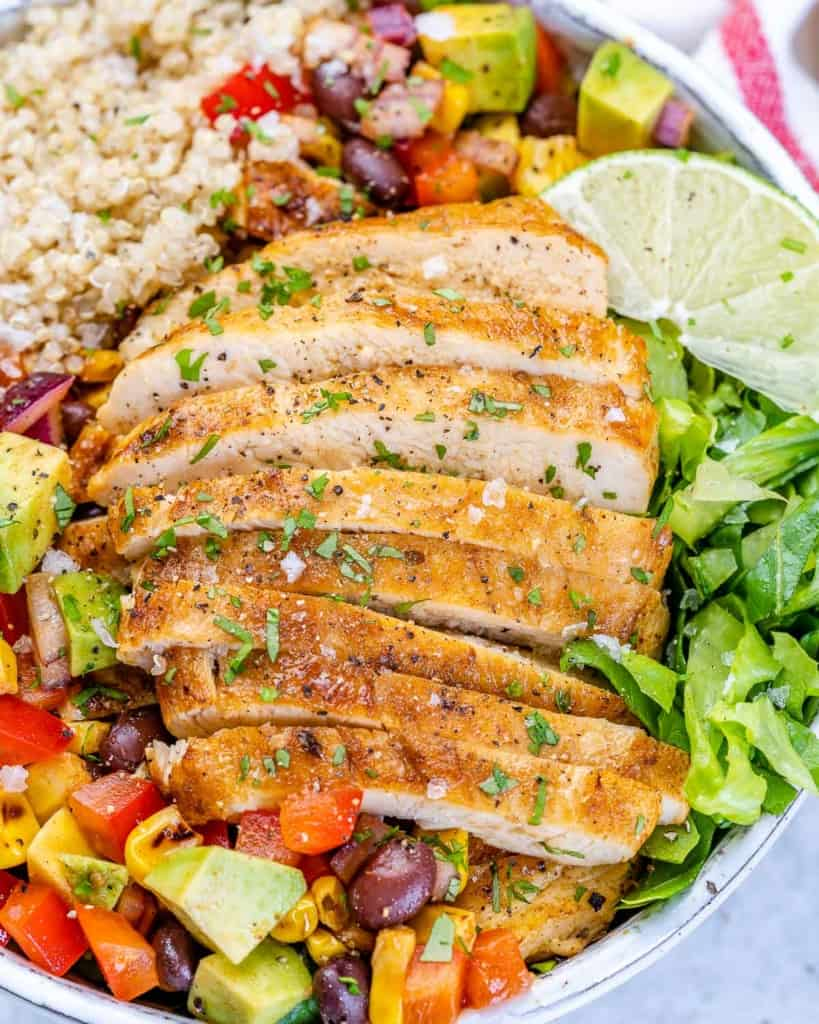 close up chicken taco bowl with sliced chicken breast over lettuce, quinoa, and black bean corn salsa