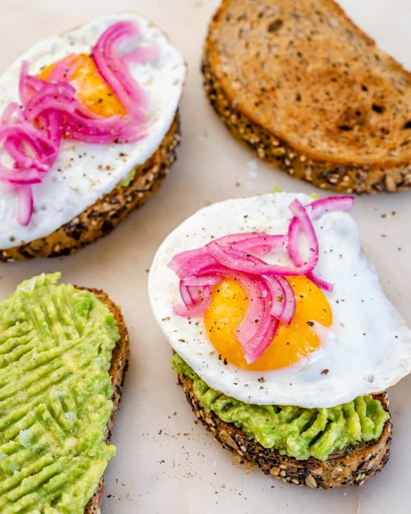 side shot of 4 toast, two topped with eggs, one with just mashed avocado and one just plain toast