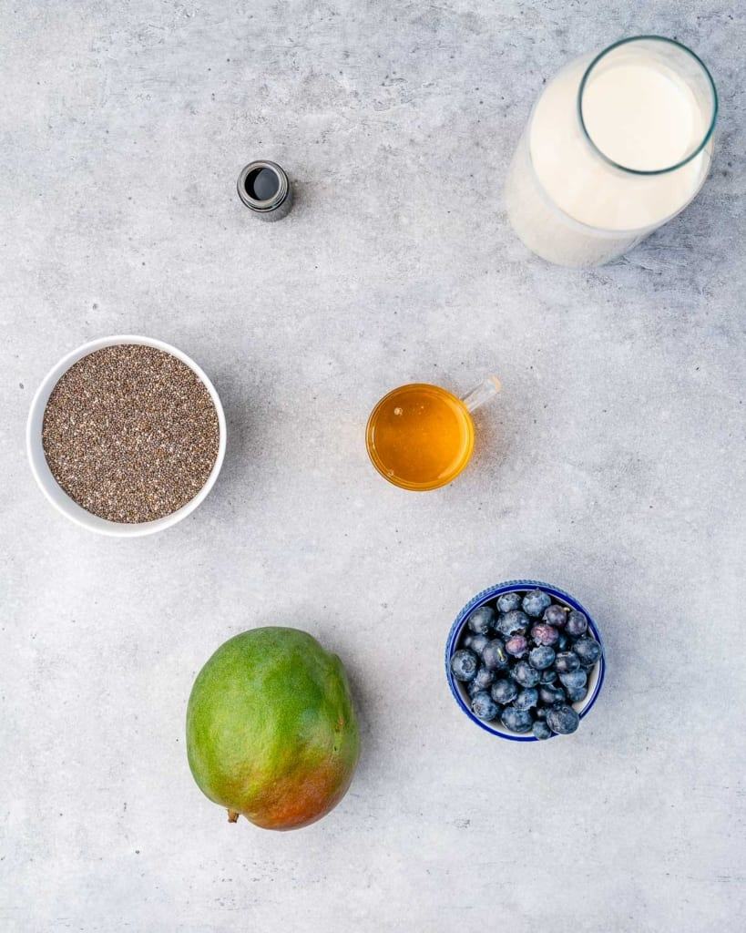 top view of ingredients to make chia pudding. Almond milk, maple syrup, vanilla, chia seeds, mango, and blueberries