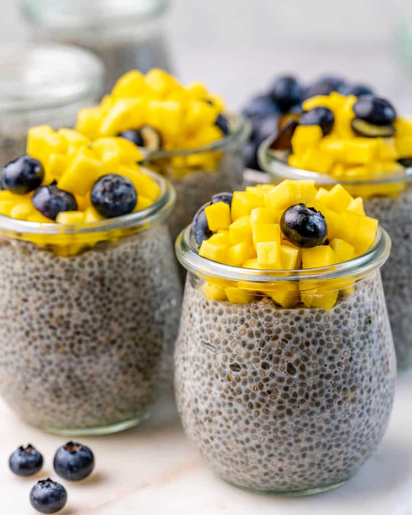 side shot of chia pudding in jars, topped with fruits.
