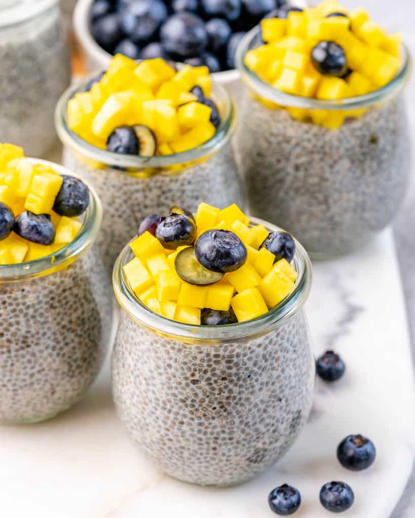 top view of jars with chia pudding topped with fruits