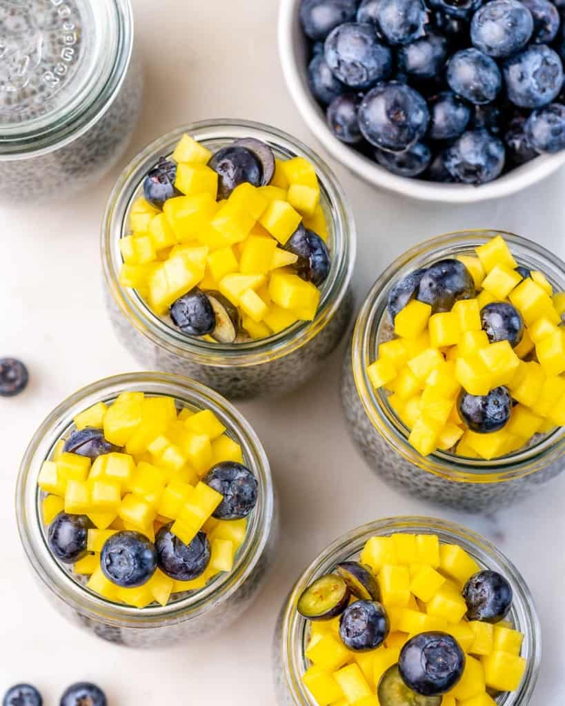 top view chia pudding in jars topped with chopped mango and blueberry