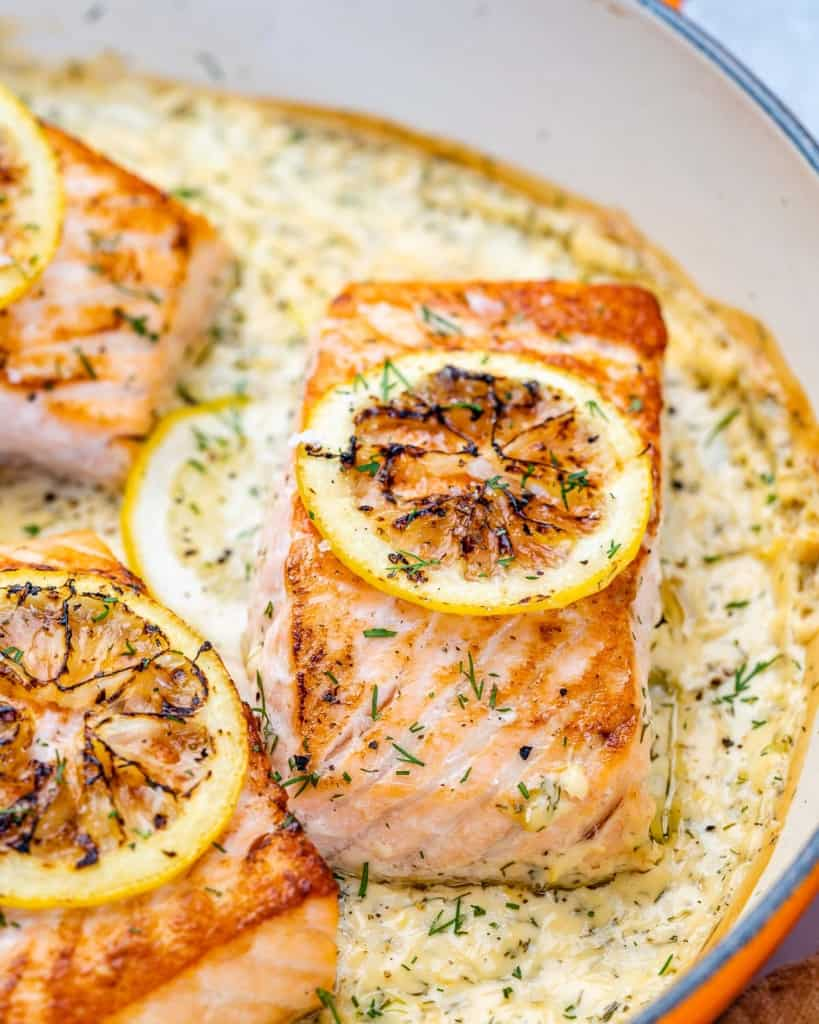 side shot of salmon filets in a creamy lemon sauce topped with slices of roasted lemons