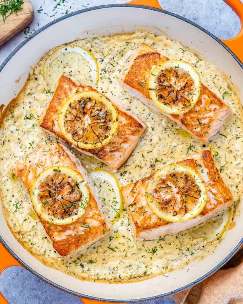 top view salmon in a creamy sauce in an orange pan