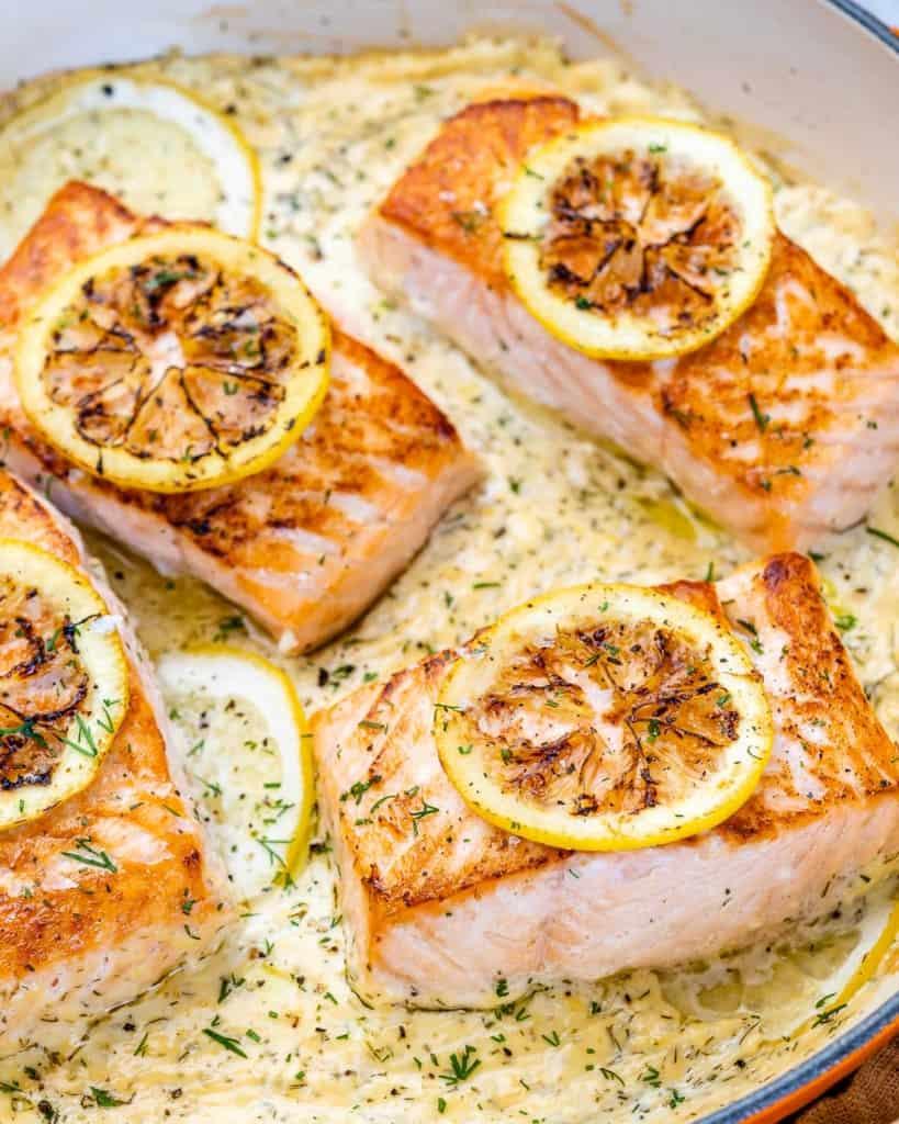 side shot of salmon filets in creamy sauce