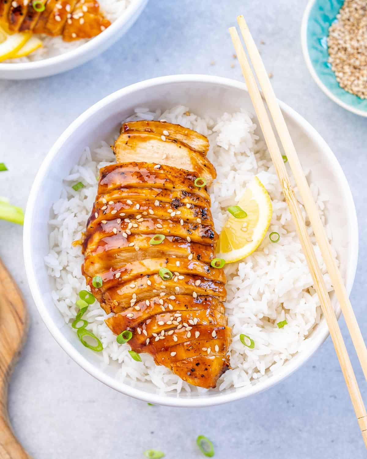 top view sliced teriyaki chicken breast over a bowl of rice