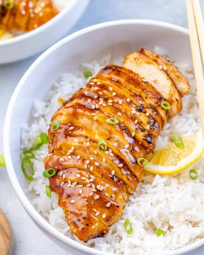 side shot of sliced baked teriyaki chicken over white rice
