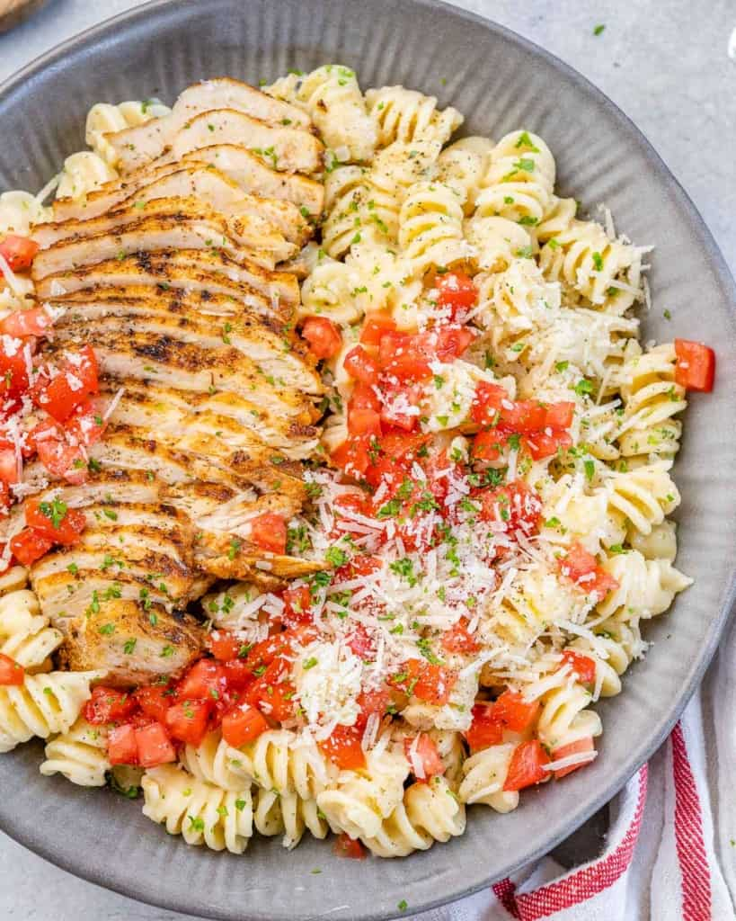 top view chicken pasta in a gray bowl topped with fresh tomatoes