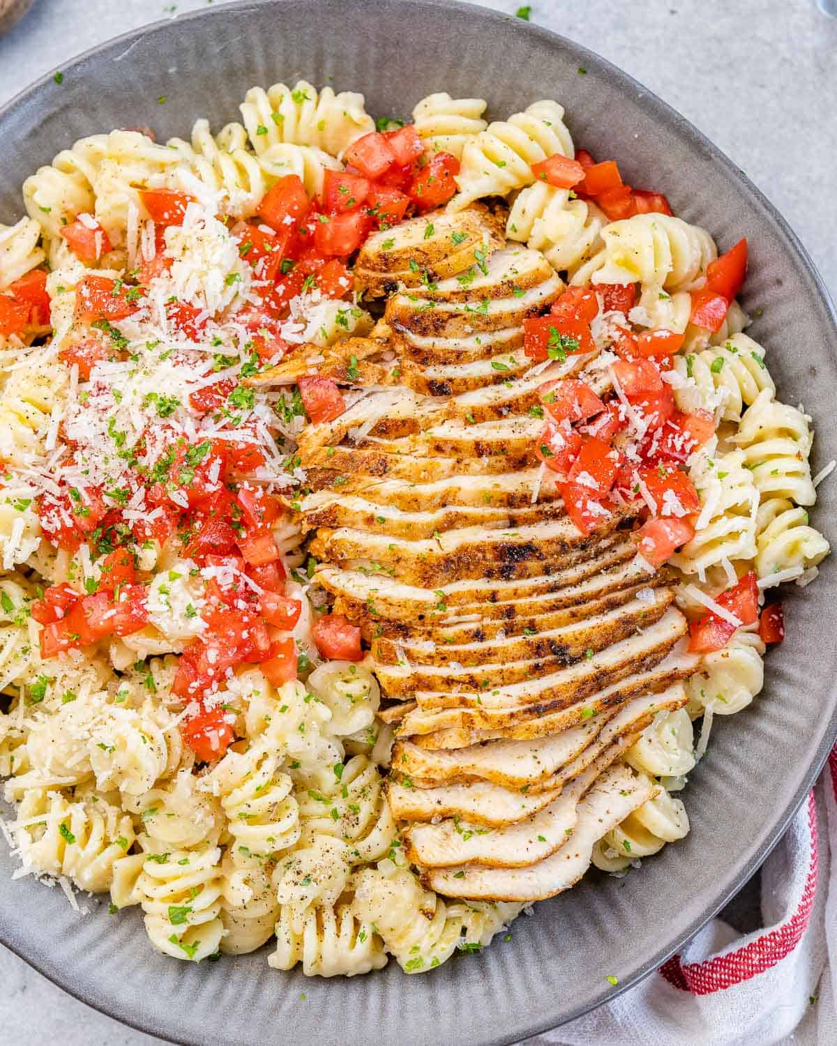 top view of pasta bowl with sliced cajun chicken breast, garnished with tomatoes and parmesan