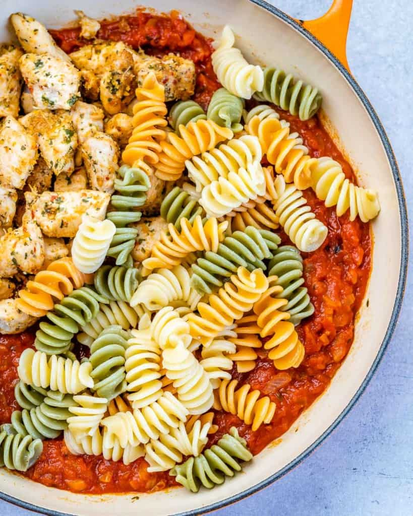 cooked pasta poured in with chicken bites and marinara sauce in the skillet.