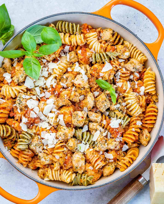 top view of chicken pasta in an orange skillet