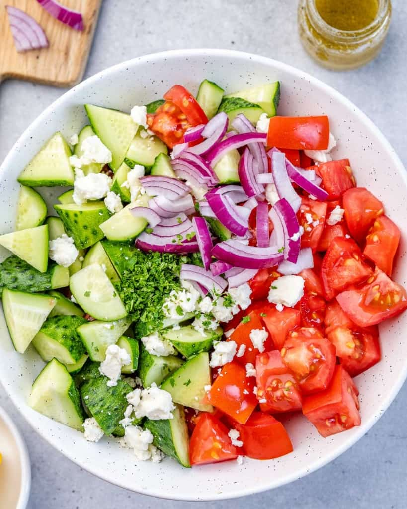 chopped cucumbers, tomatoes, onions, and feta cheese in a plate before mixing
