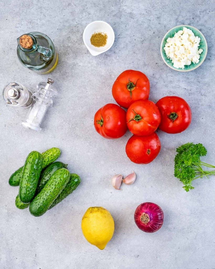 ingredients to make cucumber tomato salad with feta cheese on a blue flat surface