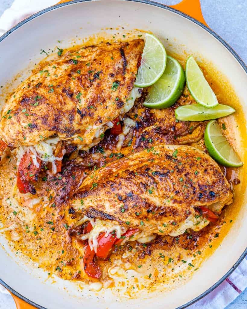 top view of chicken breast in pan with lime garnishes