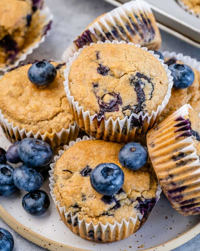 side shot of baked blueberry muffins on a plate