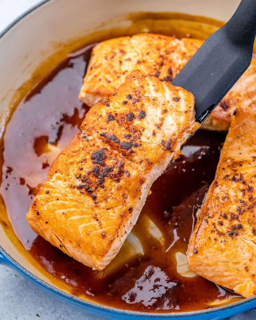 salmon filet being added back into the pan in honey sauce