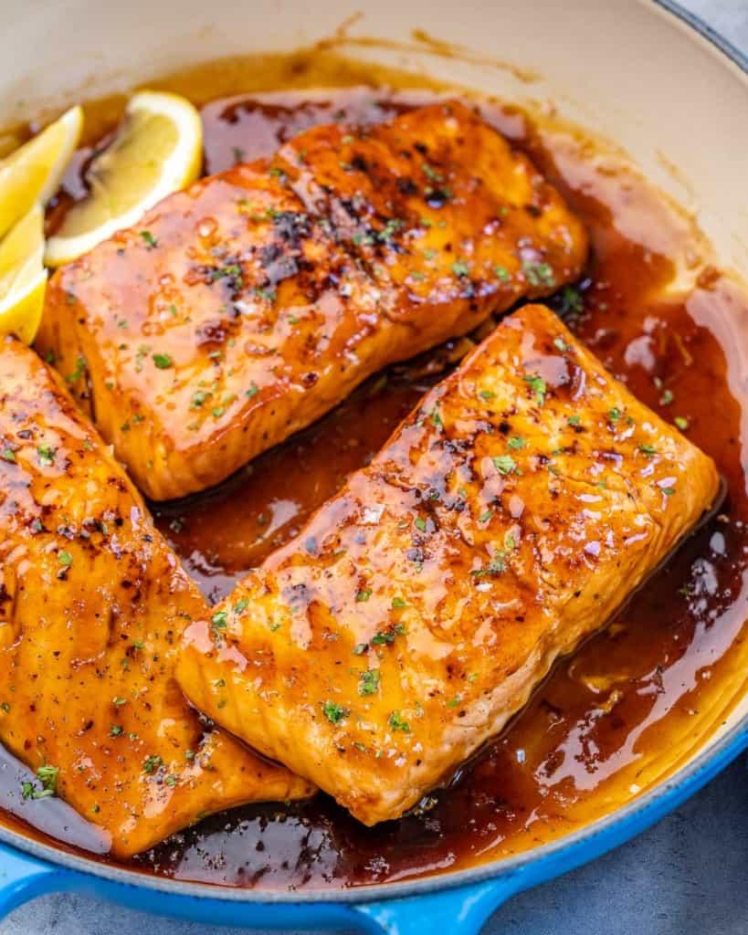 side shot of 3 honey glazed salmon filet in pan