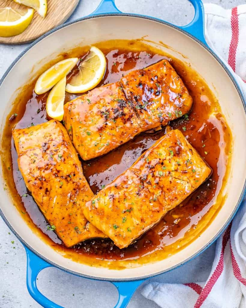 top view salmon in pan with lemon wedges for garnish