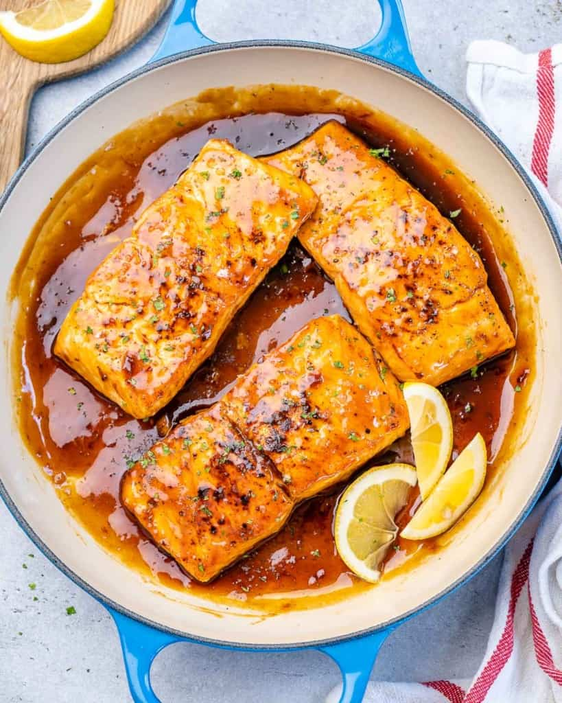 top view of 3 salmon filets on a pan with honey garlic sauce glaze