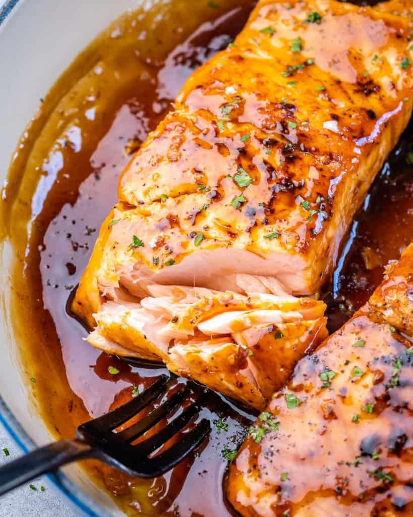 flaked salmon with fork in honey garlic sauce