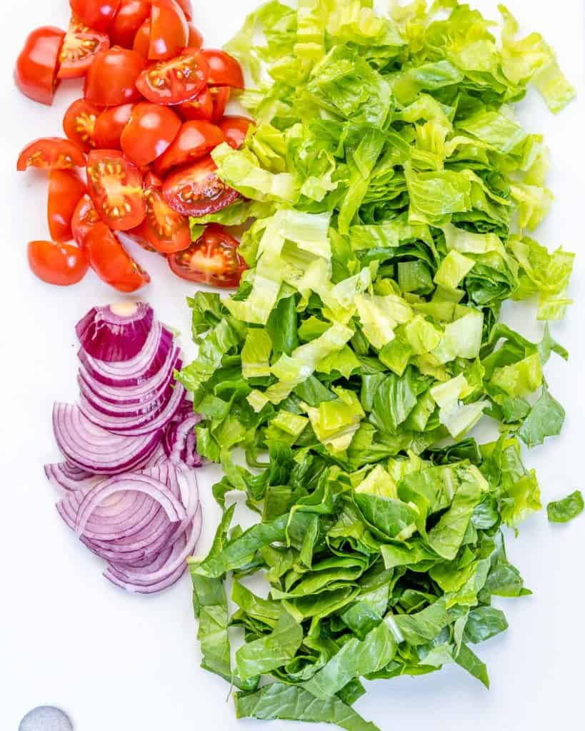 chopped lettuce, tomatoes and onions, on a white cutting board