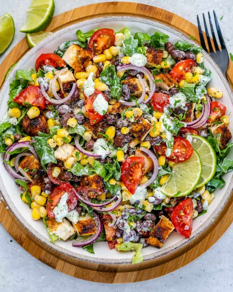 top view chicken chopped salad mixed with dressing and served in a white plate