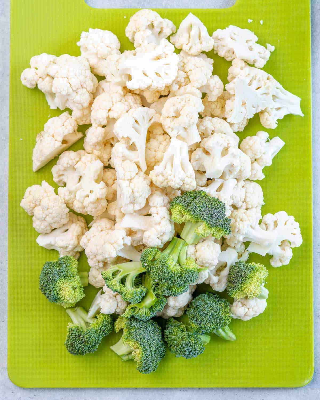 florets of cauliflower and broccoli on green cutting board