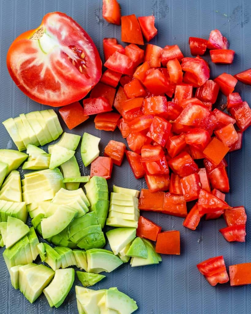 chopped tomatoes and avocados on a cutting board